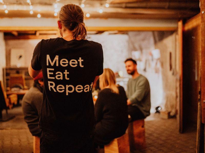 Person steht vor einer Gruppe Menschen und mit dem Rücken zu uns. auf der Rückseite des T-Shirts steht: Meet, Eat, Repeat.