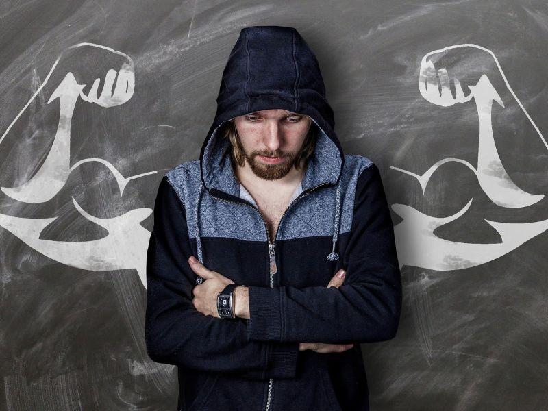 Mann steht zusammengekauert mit Blick nach unten vor einer Tafel. Auf der Tafel sind zu seinen beiden Seiten zwei muskulöse Arme aufgemalt.