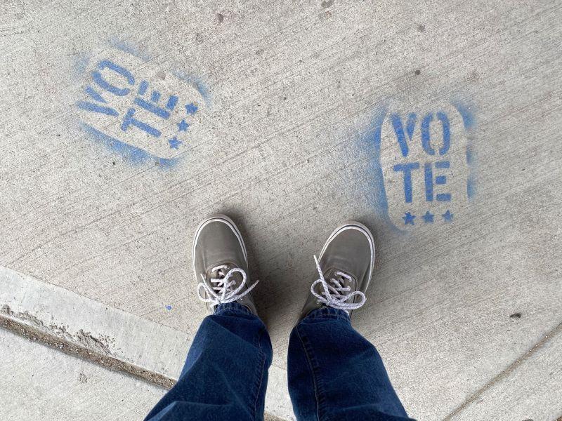 """Person in Jeans und Sneakers steht zwischen zwei blauen Schriftzügen mit dem Wort """"Vote"""" auf dem Boden"""