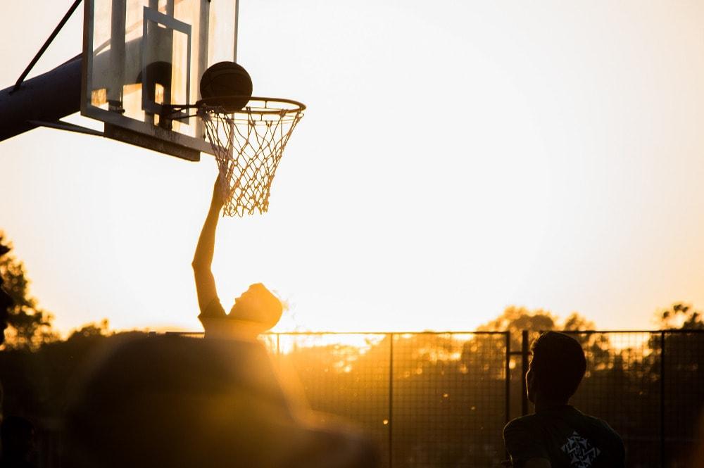 Profi-Sportler spielt Basketball im Sonnenuntergang.