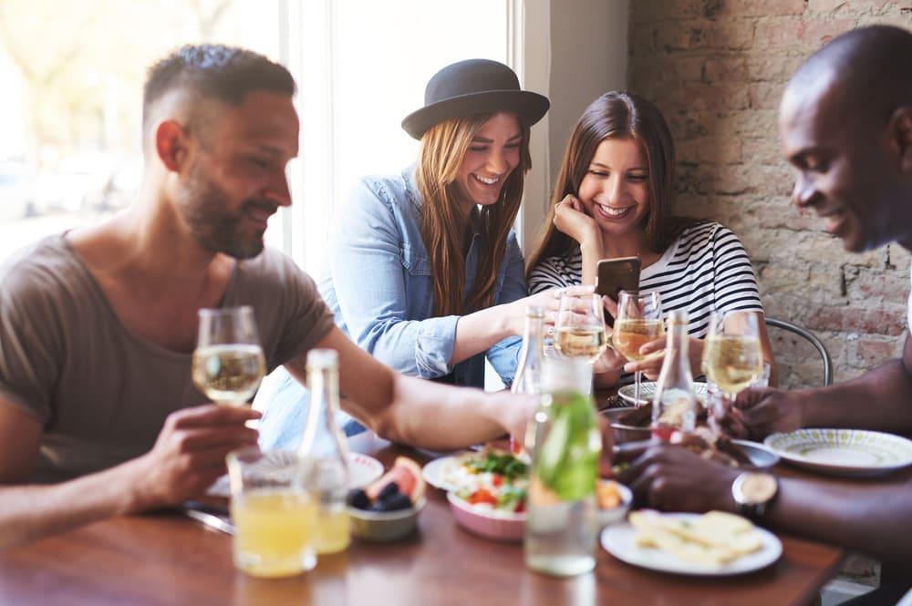 Freunde am Tisch zeigen sich Ernährungs-Apps.