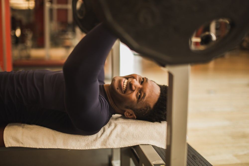 Motivations-Tricks: Personal Trainer Femi an der Hantelbank.