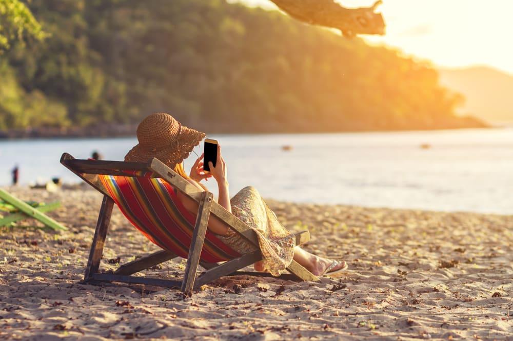 Frau am Strand nutzt Reise-Apps.