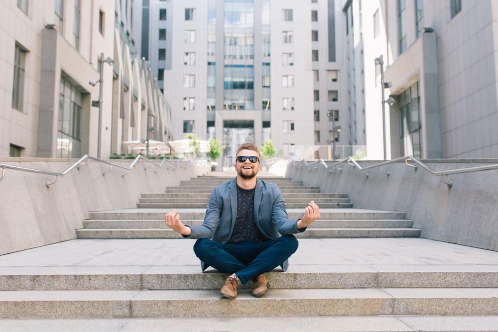 Meditation braucht kein Kloster. Mann meditiertin der Sonne vor Büro-Komplex