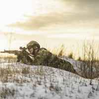 Modern war soldier army Man in multicam camouflage is lying and aiming aim at the sight. full equipment commandos with helmet and weapon gun. lying and shooting soldier. modern warfare battlefield.
