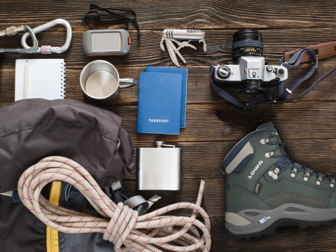 Travel items near backpack on the floor for mountain trip with retro camera, passports, GPS, boots, retro camera, flask and hiking equipment, top view