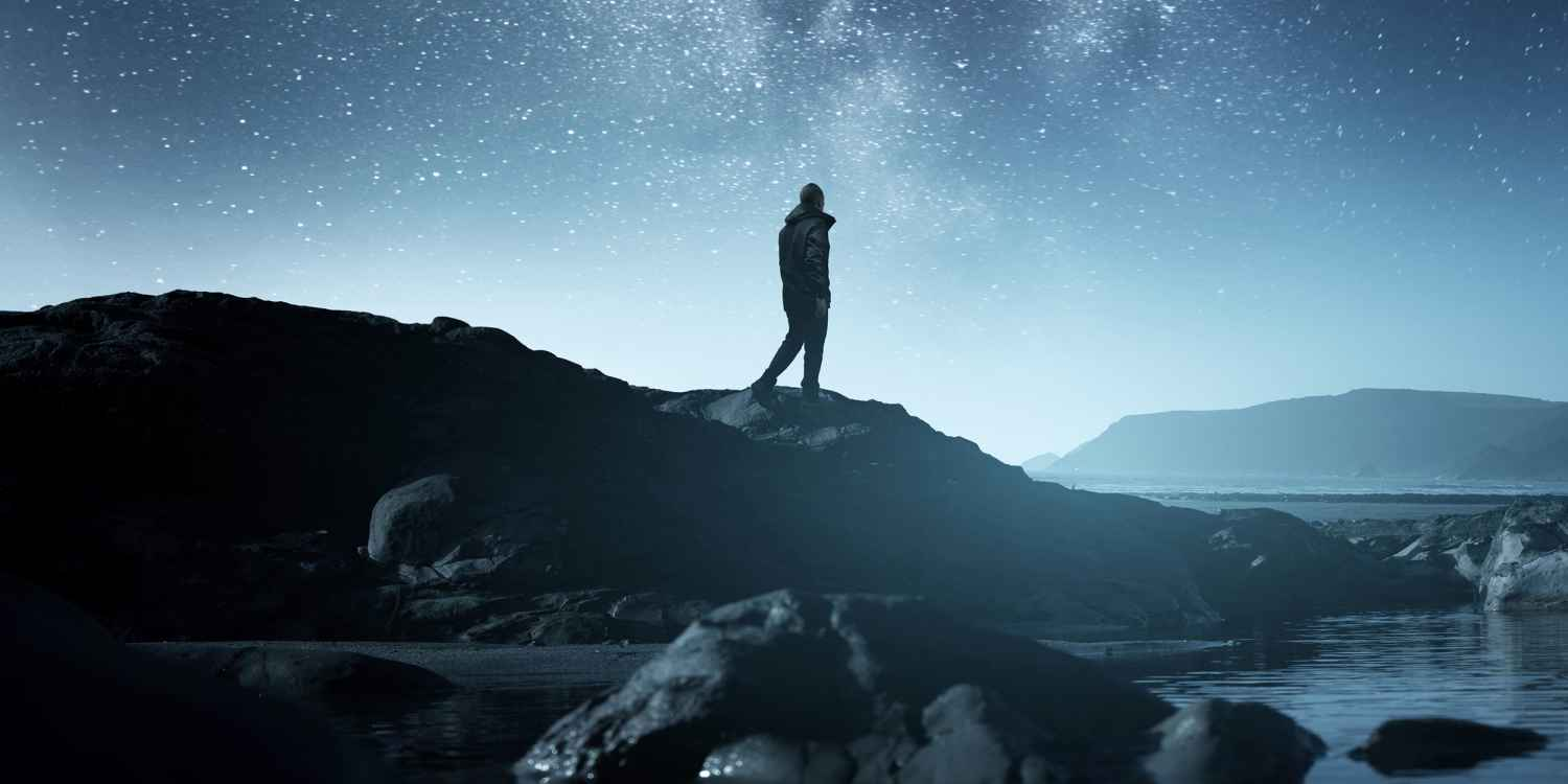 Calm Midnight adventures. A long exposure shot of a man staring up into the night sky, silhouetted against the milky way galaxy. Photo composite.