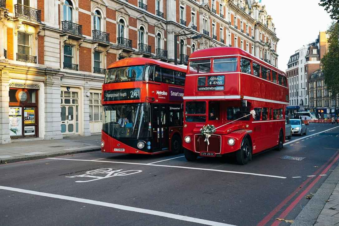 Two red buses driving through London