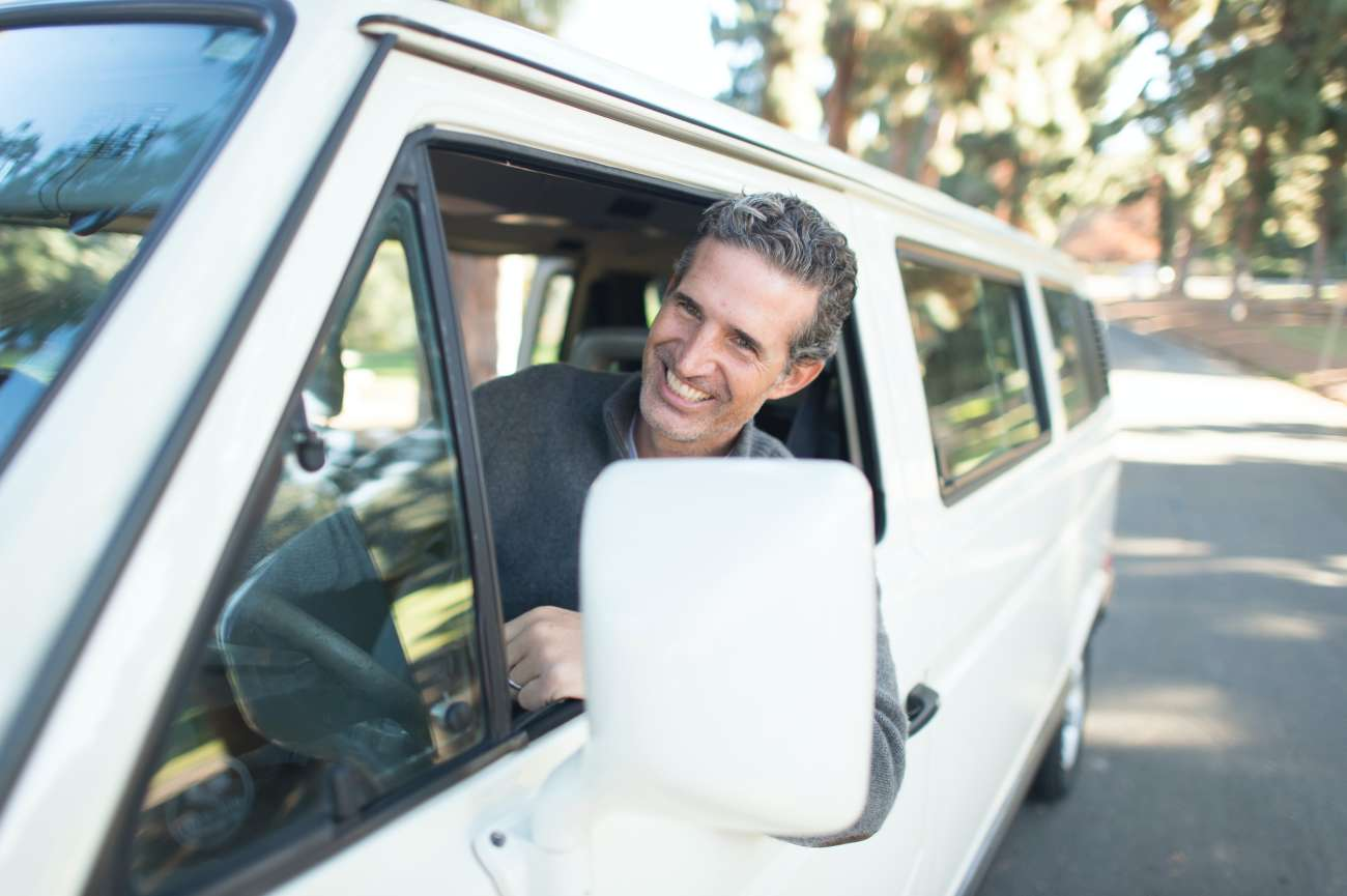 A man smiling leaning out of the window of his van