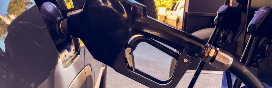 A large black fuel pump rests in the rests in the fuel filler of a vehicle, with the owner certain they aren't putting unleaded petrol in a diesel car