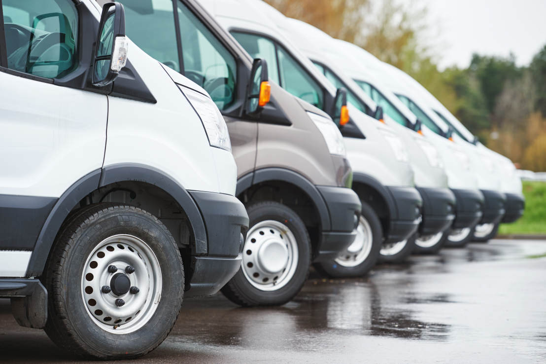 A line of parked vans that form part of a fleet of vehicles