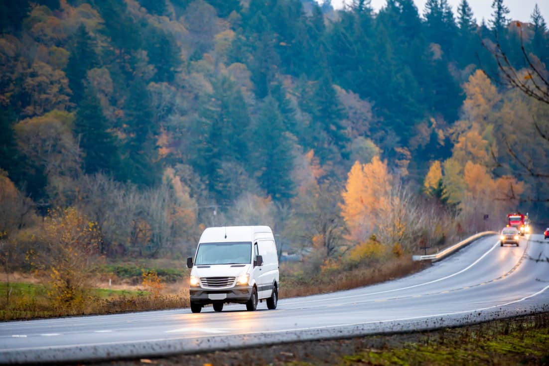 A van driving down a road with forest trees in the background