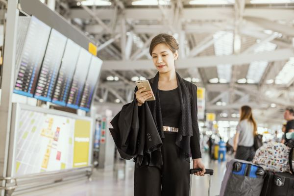 Business woman at airport on business mobile
