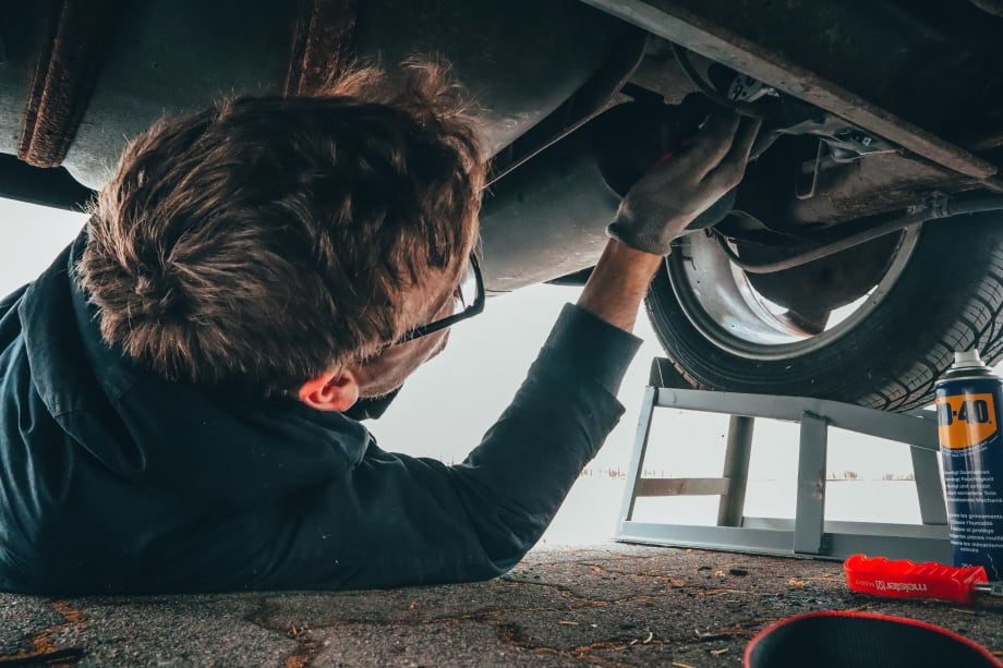 A man looks under his car as part of his car maintenance checks, which include tyre pressure checks
