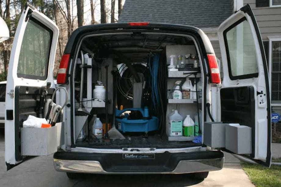 A van with it's back doors open showing work tools