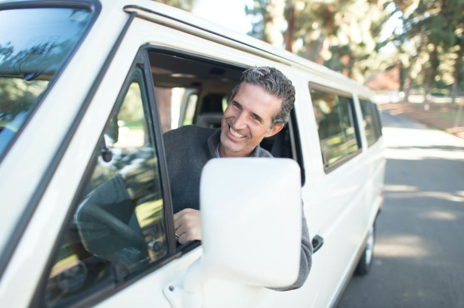 Happy man leaning out van window
