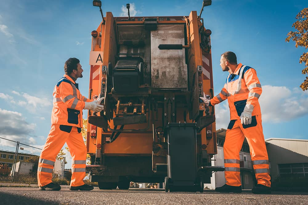 Two refuse workers emptying bins into their truck