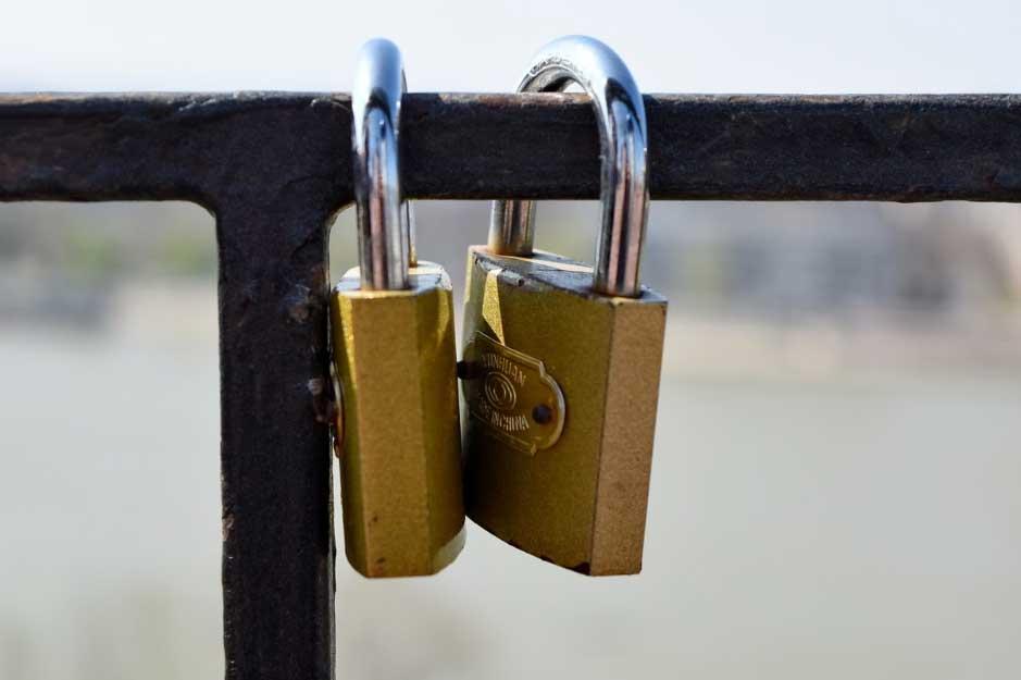 Two padlocks on metal fence