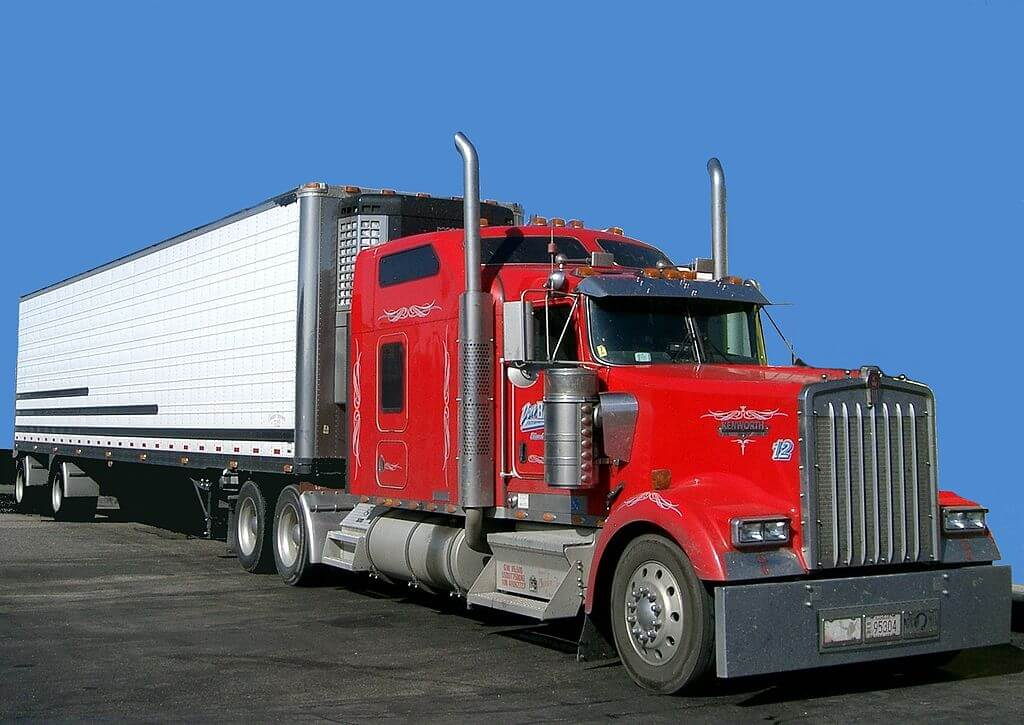 A large red truck with a white haulage section