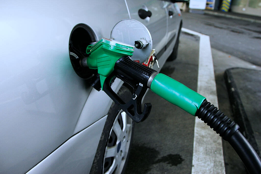 A silver car being fuelled with unleaded petrol