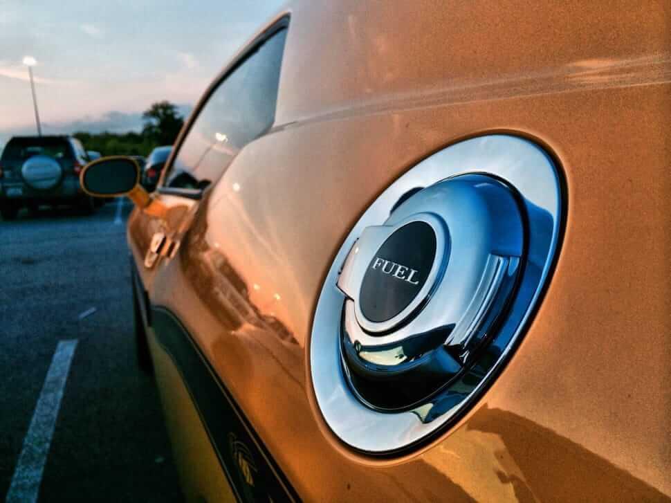 Un ugello del carburante color argento su un veicolo arancione