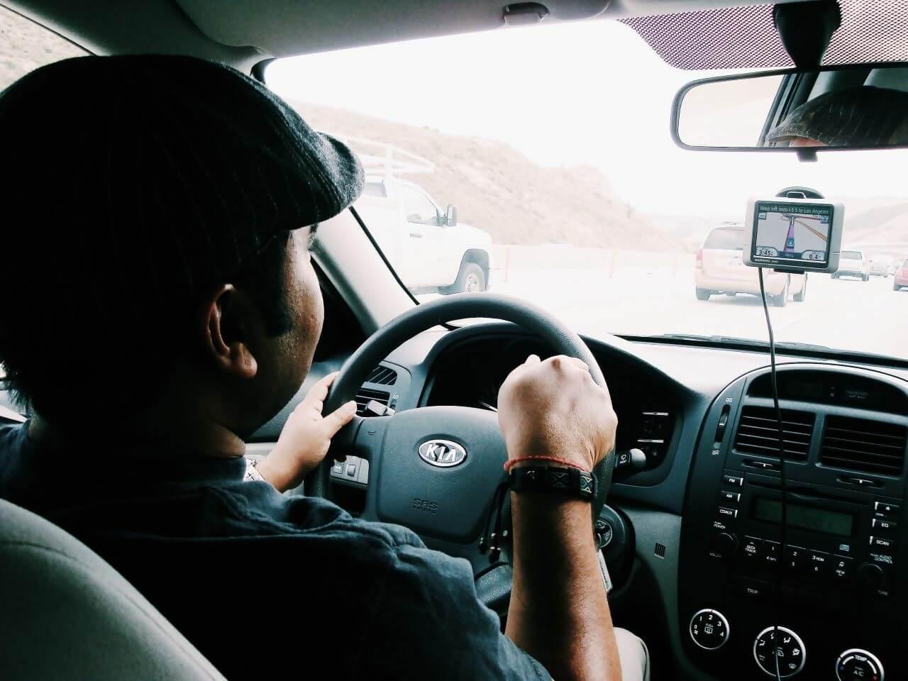 Man driving a Kia car with sat nav
