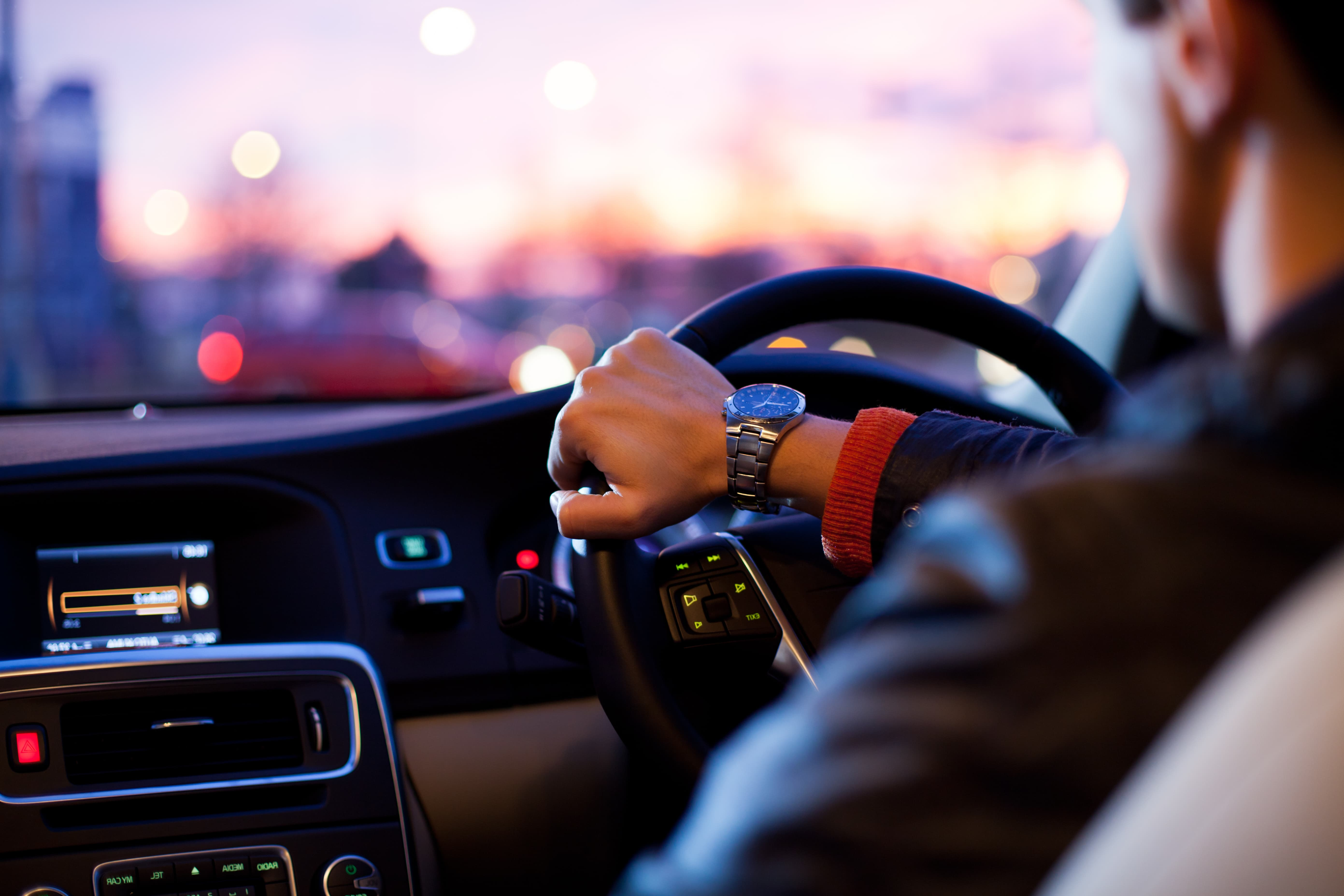 A man driving a car at dusk