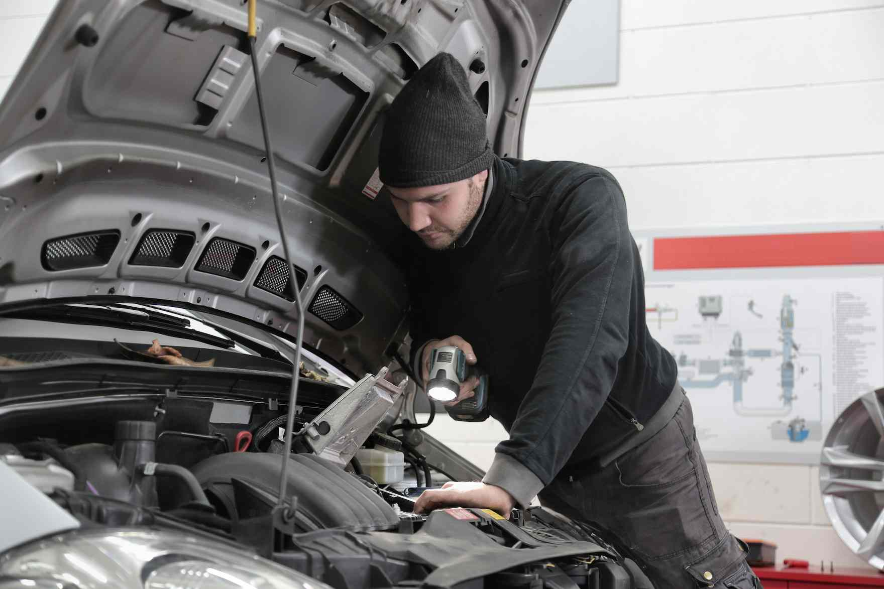 A man in a black beanie hat looks under the bonnet of a car made by the volkswagen car manufacturers that has the volkswagen polo model name