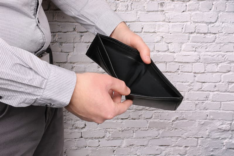 A male, small business owner holds an empty wallet because he used all his cash to cover an important business expense