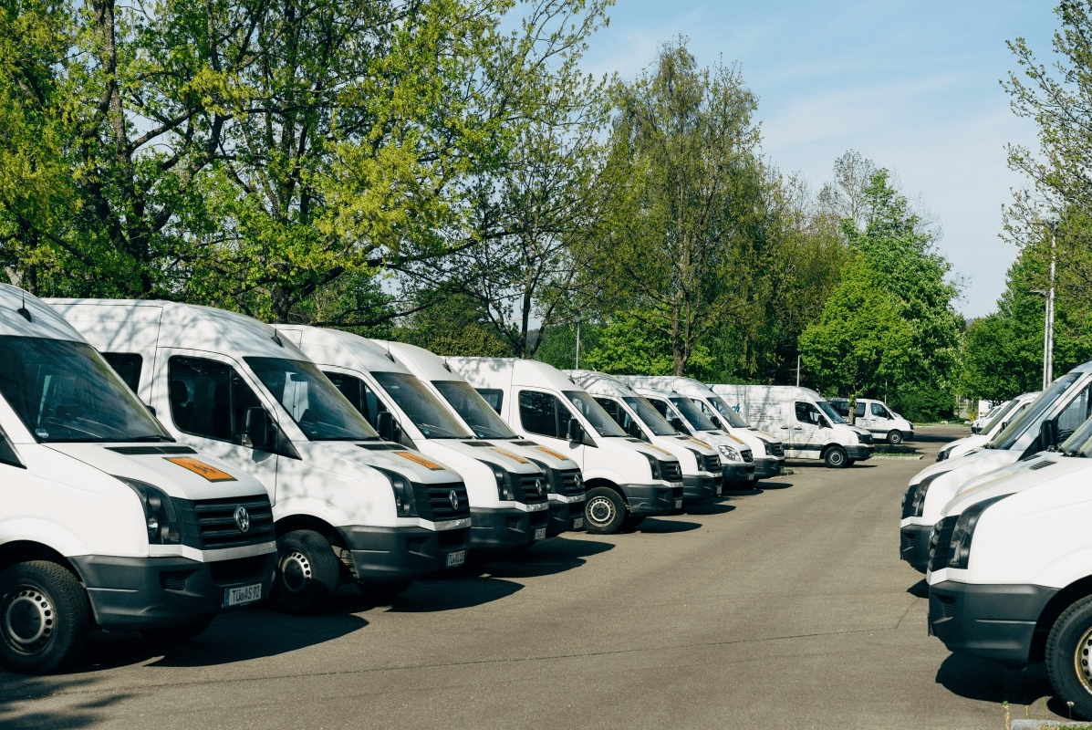 A row of white vans are parked