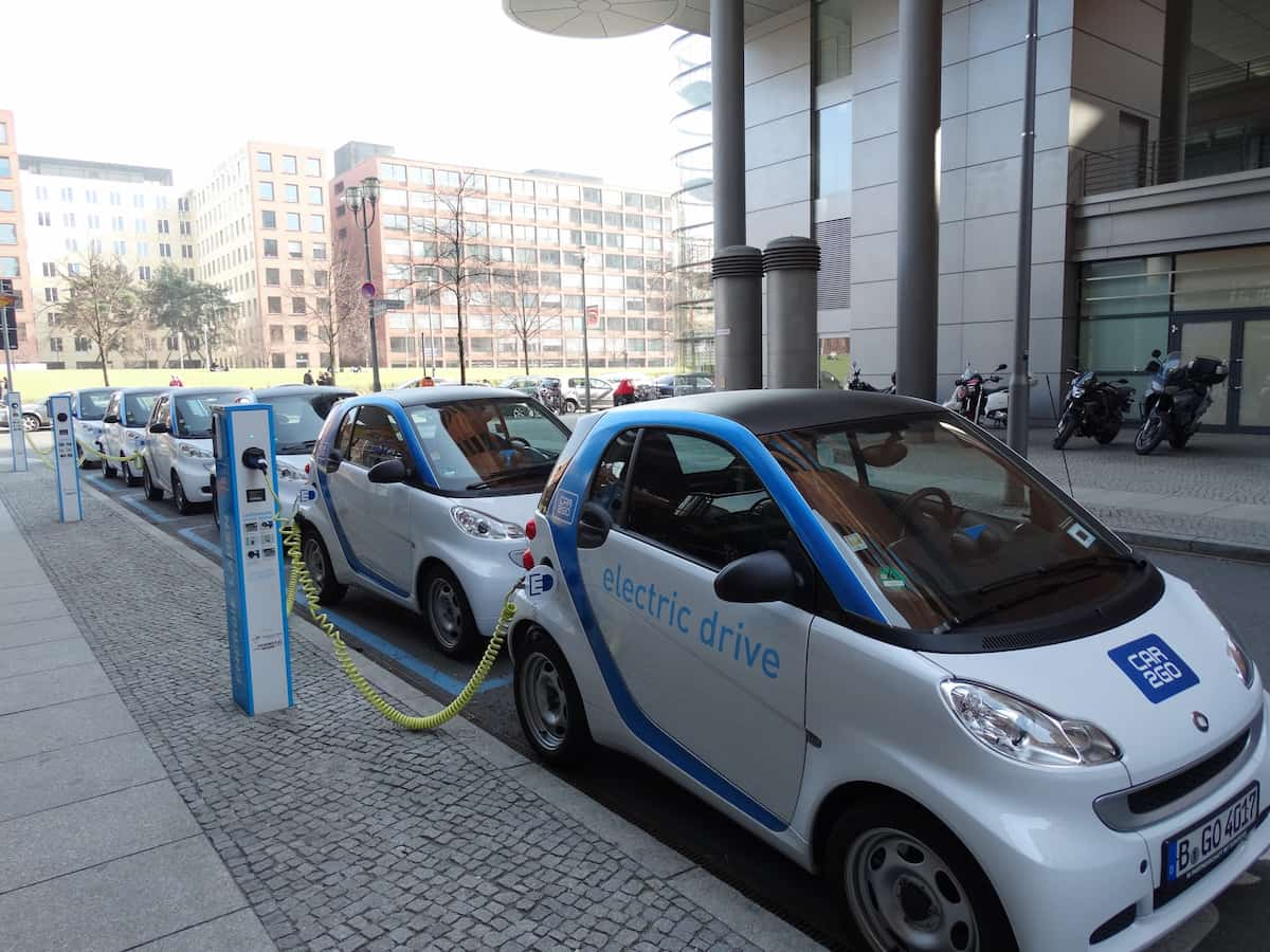 Six white electric cars being charged at a public charging station