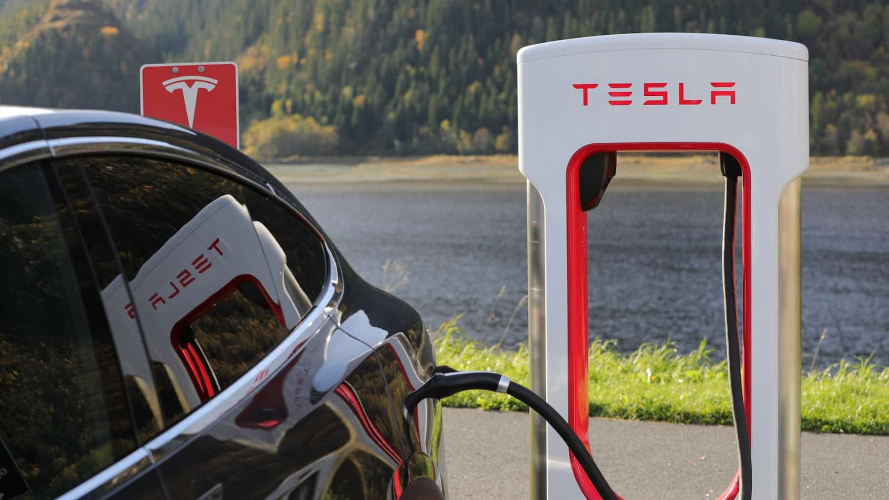 A black Tesla is charged at a Tesla charging point by a lake