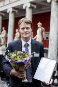 A photo of Mads Gyrd-Hansen with a bunch of flowers after receiving his honour