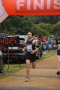 Male runner runs through finish line