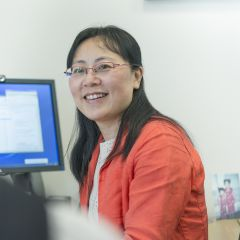 A profile picture of Xin Lu sitting with a computer in the background