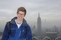 Photo of smiling second-year male student Jonas Sandbrink standing in front of a city view with skyscrapers under an overcast sky
