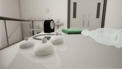 Essential resuscitation equipment (different small masks, a bag-valve ventilation device to deliver positive pressure ventilation, a clock and dry pre-warmed clean towels neatly arranged on the trolley for the player to interact with.