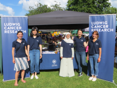 5 Ludwig Oxford researchers standing in front of the stand at the Headington Festival in bright sunshine