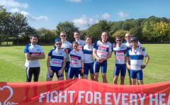 Ludwig Oxford cycling team members wearing their matching Ludwig Cancer Research cycling outfits posing for a photo in a green field on a sunny day