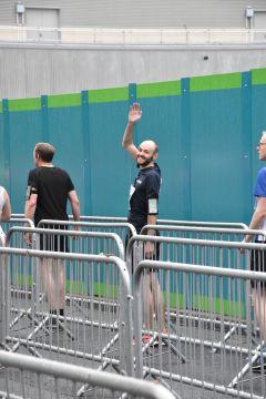Waving male runner standing behind barriers.