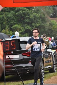 male runner with car in background