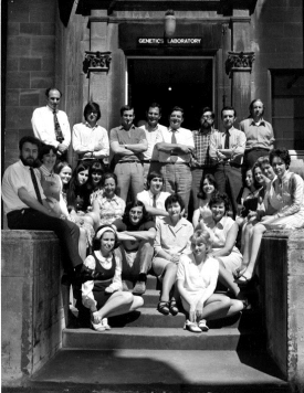 A large class of male and female students in front of the laboratory facing the camera