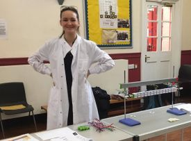 Olivia Lombardi dressed in a white lab coat standing by the DNA decoding and mutations public engagement activity in a school hall.