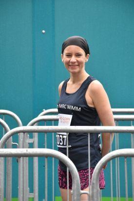 Smiling female runner standing behind barriers.