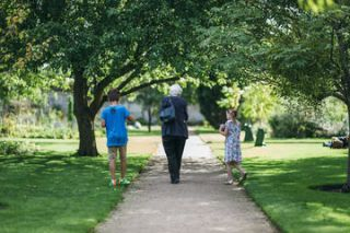 older lady walking through the Botanical Gardens with a young boy and girl at her either side of her