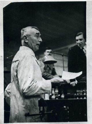 G G Douglas in a lab coat addressing students