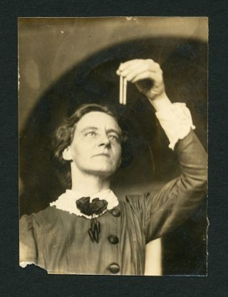 Sepia photograph of Mabel Purefoy Fitzgerald examining a scientific sample in a pipette.
