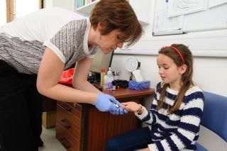Dr Ann Van den Bruel performs a diagnostic test.