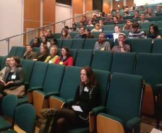 Postdocs sat in a lecture theatre watching the talks