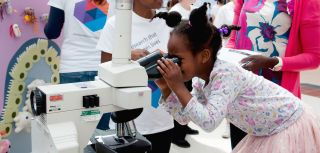 Little girl looks down the microscope